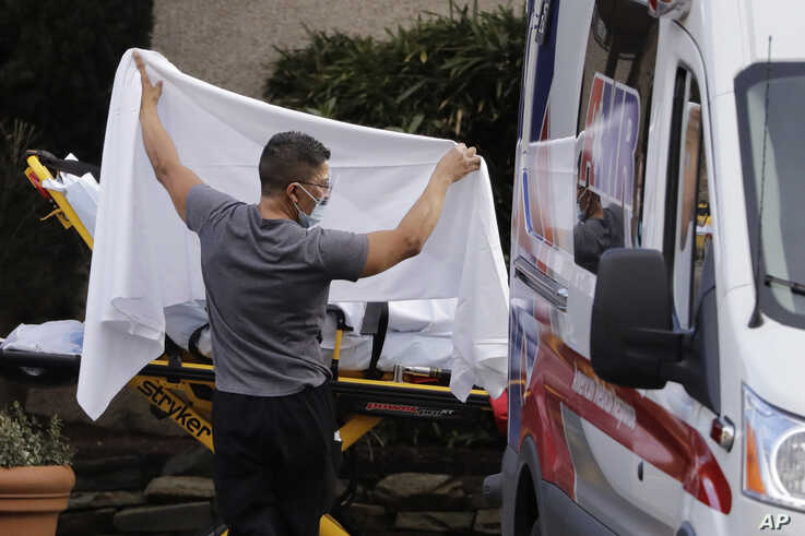 A man blocks the view as a person is taken by a stretcher to a waiting ambulance from a nursing facility where more than 50…