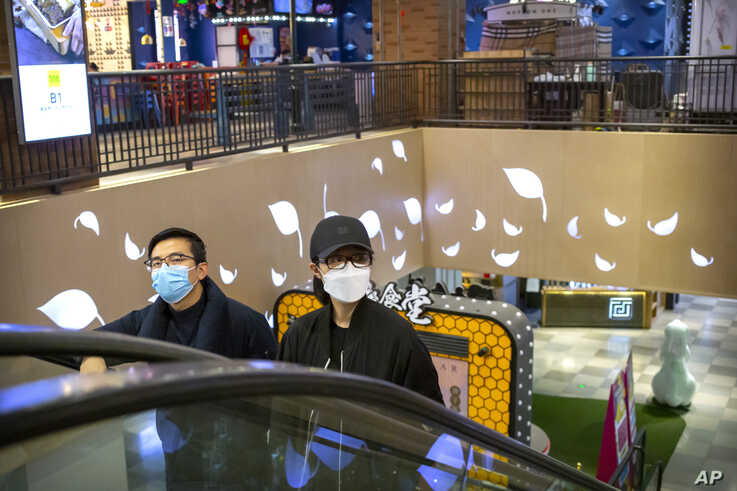 A couple wear face masks as they ride an escalator at a shopping mall in Beijing, Saturday, March 7, 2020. Crossing more…