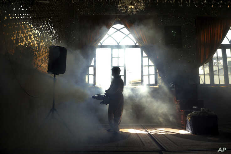 A firefighter disinfects the shrine of Saint Saleh to help prevent the spread of the new coronavirus in northern Tehran, Iran,…