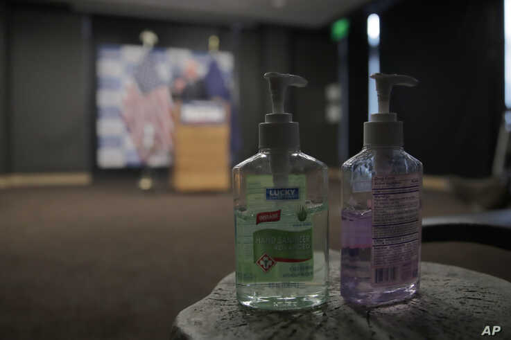 Hand sanitizer are placed near reporters as Democratic presidential candidate, Sen. Bernie Sanders, I-Vt., speaks about…