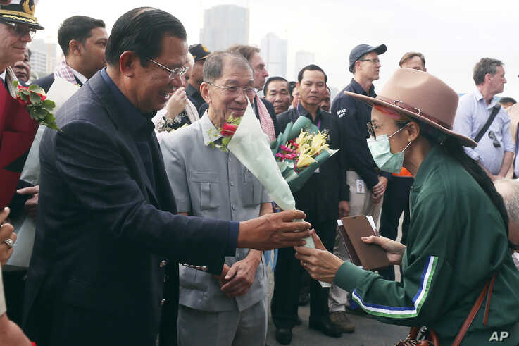 FILE - In this Feb. 14, 2020, file photo, Cambodia's Prime Minister Hun Sen, left, gives a bouquet of flowers to a passenger…