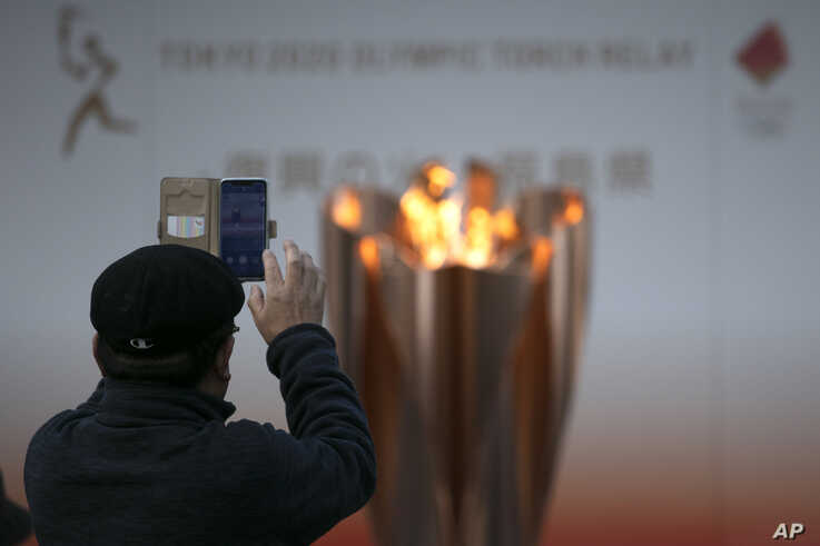 A man takes pictures of the Olympic Flame during a ceremony in Fukushima City, Japan, Tuesday, March 24, 2020. The Tokyo…