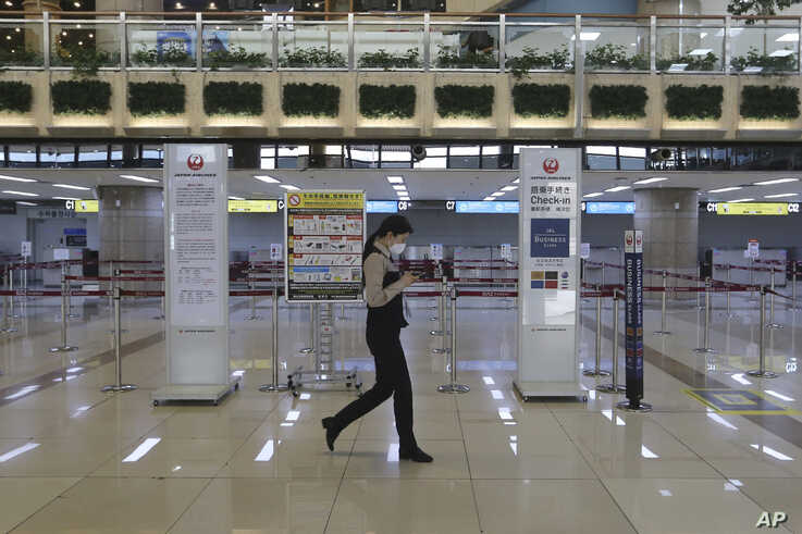 A Gimpo Airport official wearing a face mask passes by check-in counters of Japan Airlines at Gimpo Airport in Seoul, South…