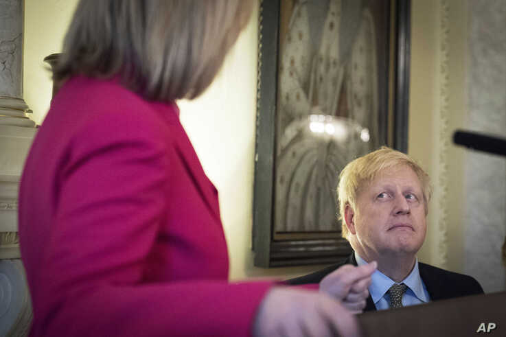 Britain's Prime Minister Boris Johnson listens to British politician Liz Truss during a panel event and reception to mark…