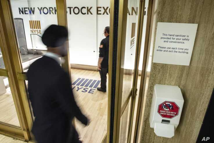 A hand sanitizer dispenser is installed at the entrance to the New York Stock Exchange trading floor, Tuesday, March 3, 2020…