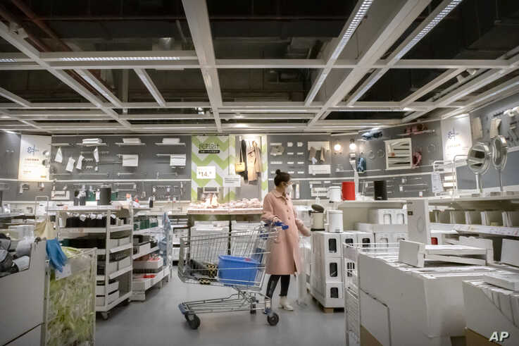 A woman wears a face mask to protect against coronavirus infection as she shops at an IKEA store in Beijing, Saturday, March 21…