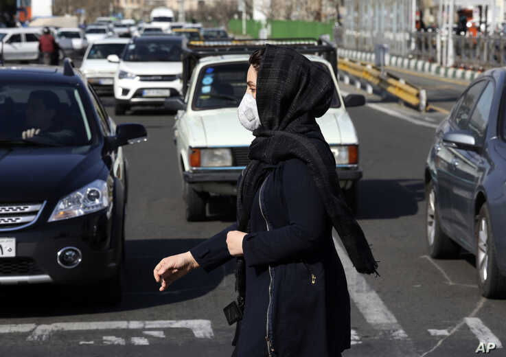 A woman wearing a face mask crosses an intersection in northern Tehran, Iran, Wednesday, March 4, 2020. With deaths spiking in…