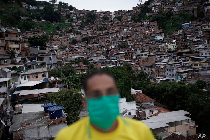 A member of a cultural center wears a mask to protect himself against the spread of the new coronavirus, as he donates food for…