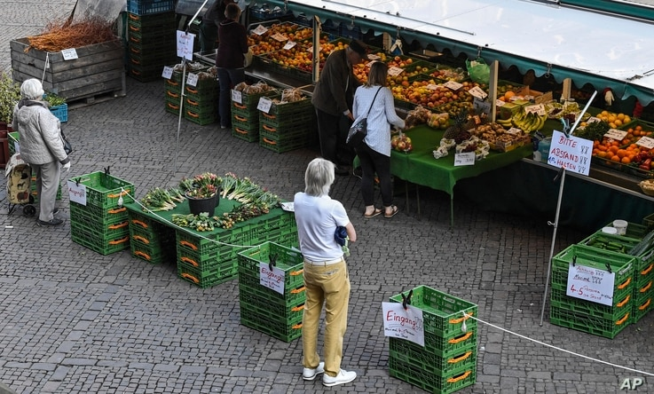 People keep distance due to the coronavirus at a market in Aachen, Germany, Thursday, April 9, 2020. In order to slow down the…