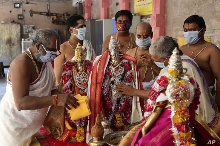 Hindu priests wearing face masks perform rituals during 'Ram Navami' festival at a temple closed for devotees as part of…