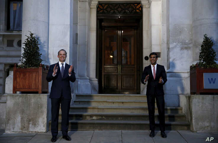 Britain's Foreign Secretary Dominic Raab, left, and Chancellor Rishi Sunak cap outside the Foreign and Commonwealth Office…