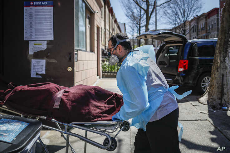 Employees deliver a body at Daniel J. Schaefer Funeral Home, Thursday, April 2, 2020, in the Brooklyn borough of New York. The…