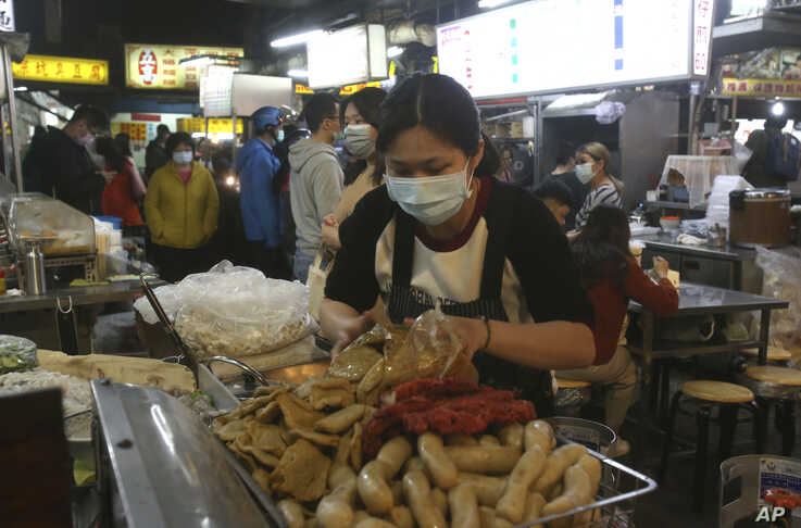 A vendor wears face mask to help curb the spread of the coronavirus and waits for customers at a night market in Taipei, Taiwan…