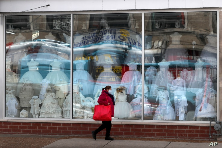 A woman wearing a protective mask walks past a closed children's clothing store in the Hispanic, Little Village in Chicago,…