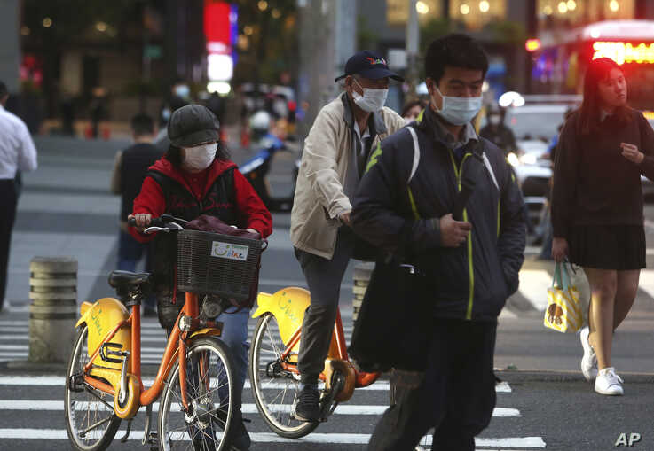 People wear face masks to protect against the spread of the coronavirus in Taipei, Taiwan, Tuesday, March 31, 2020. The new…