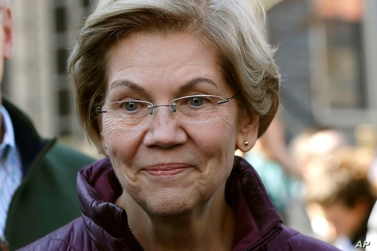 FILE - In this March 5, 2020, file photo, Sen. Elizabeth Warren, D-Mass., speaks to the media outside her home in Cambridge,…