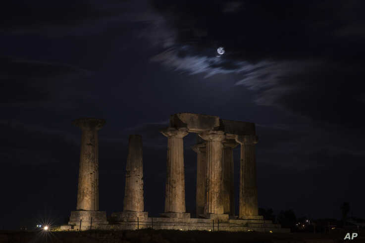 The super moon rises in the sky in front of the Apollo's temple about 80 kilometers (50 miles) southwest of Athens on Tuesday,…