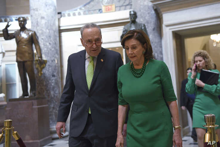 Senate Minority Leader Sen. Chuck Schumer of N.Y., and House Speaker Nancy Pelosi of Calif., walk as they head to a lunch with…