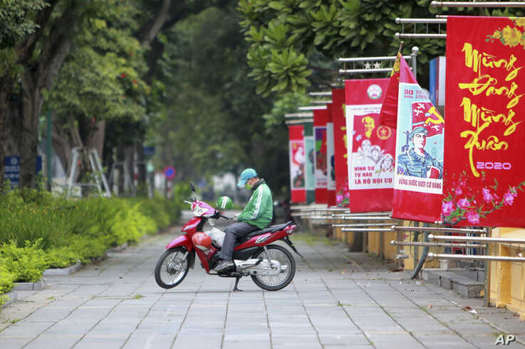A delivery man waits for online order outside a cafe in Hanoi, Vietnam, Wednesday, April 1, 2020. Vietnam on Wednesday starts…