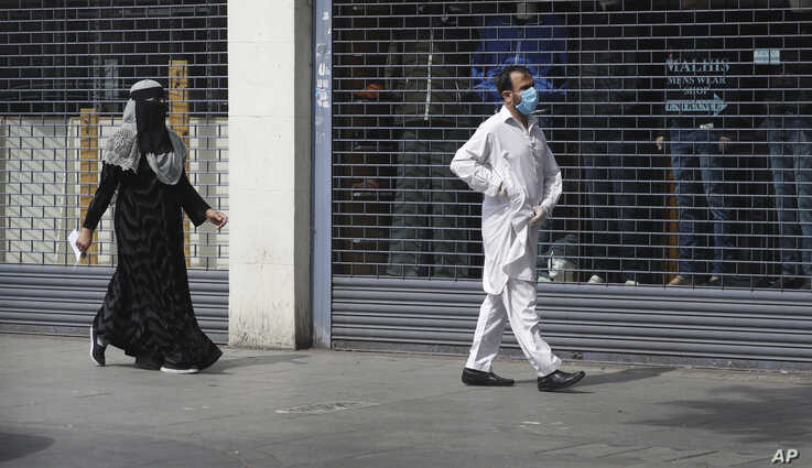 A man wearing a face mask to protect against coronavirus and a woman, walk past shuttered shops on a usually bustling high…
