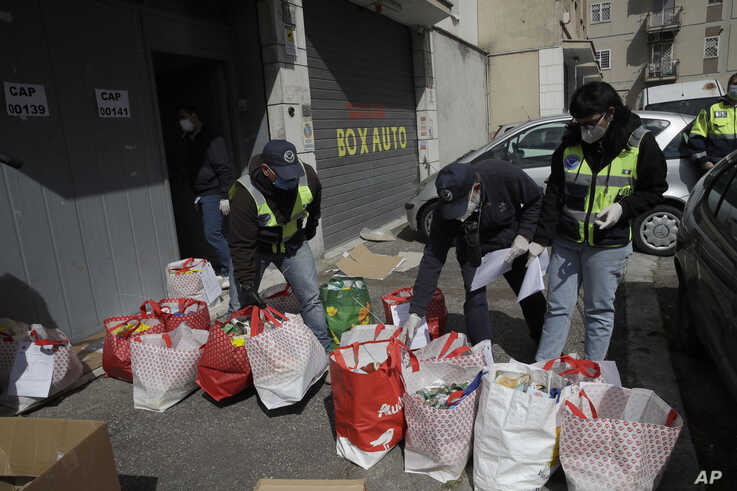 Civil protection volunteers prepare bags with food donated by residents at their headquarters in Rome's working class Tufello…