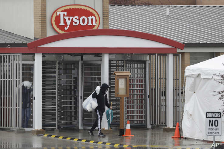 A Tyson Fresh Meats plant employee leaves the plant, Thursday, April 23, 2020, in Logansport, Ind. The plant will temporarily…