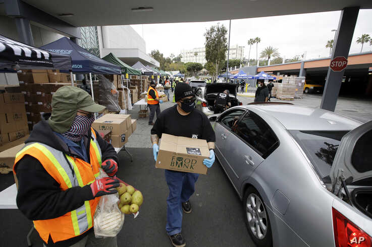 Volunteers load up vehicles at a food distribution center Friday, April 17, 2020, in the Crenshaw district of Los Angeles. Food…