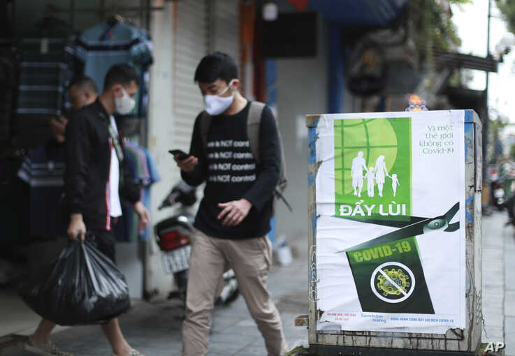 "People walk by a poster reading in Vietnamese ""Fighting COVID-19"" in Hanoi, Vietnam on Thursday, Apr. 23, 2020. Business…"