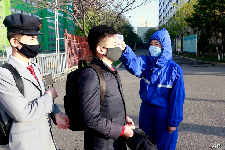 A student wearing a face mask has his temperature checked as a precaution against a new coronavirus as their university…