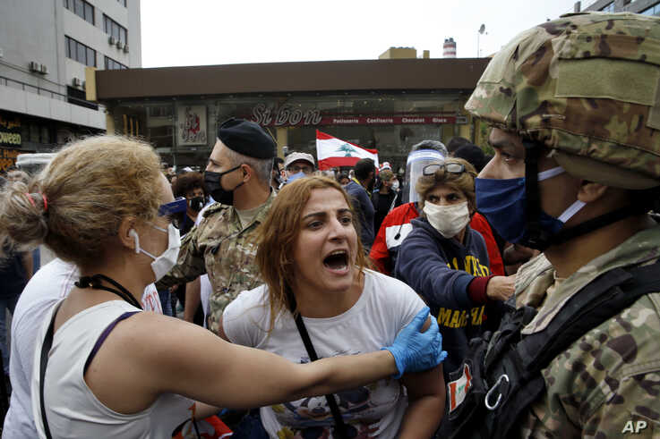 An anti-government protester scuffles with Lebanese army soldiers in the town of Zouk Mosbeh, north of Beirut, Lebanon, Monday,…