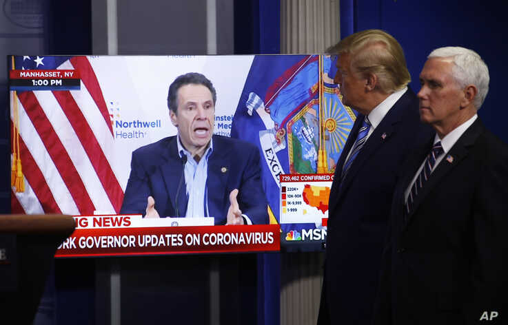 Vice President Mike Pence, right, and President Donald Trump watch a video of New York Gov. Andrew Cuomo speaking during a…