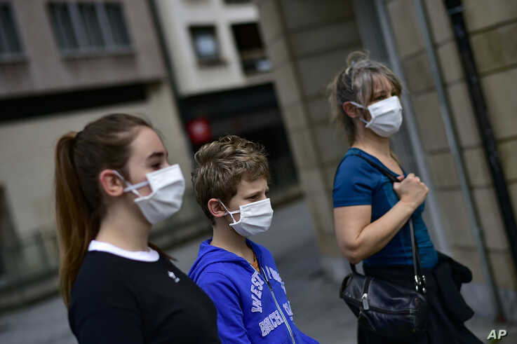 A family wearing face mask to protect of the coronavirus go for a walk, in Pamplona, northern Spain, Sunday, April 27, 2020. On…