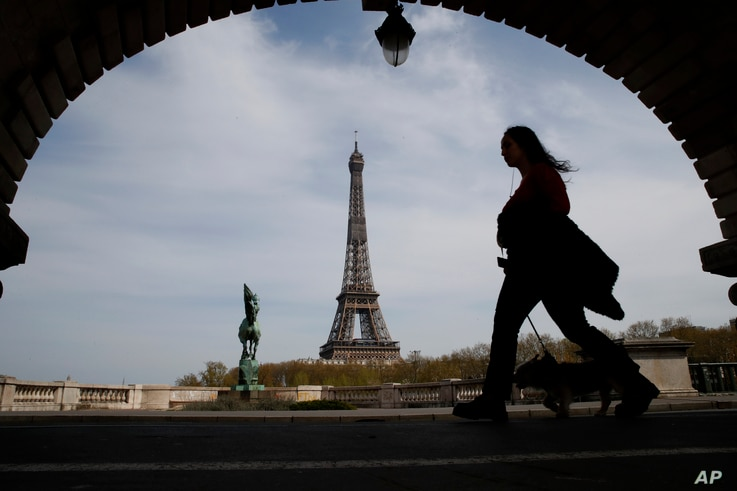 A woman walks her dog on a Paris bridge, with the Eiffel tower seen in background, during a nationwide confinement to counter…