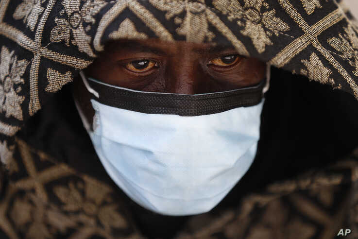 A man wears a protective mask while waiting for a bus in Detroit, Wednesday, April 8, 2020. Detroit buses will have surgical…
