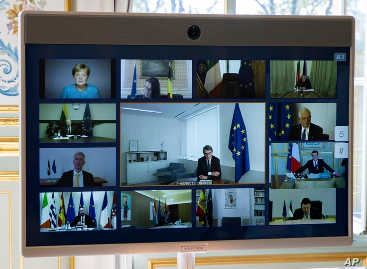 Members of the European Council are seen on the screen during a video conference call at the Elysee Palace in Paris, Thursday…