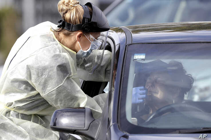Medical staff test a shopper in her car who volunteered at a pop-up community COVID-19 testing station at a supermarket carpark…