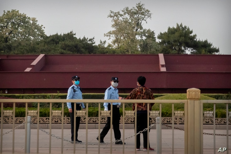 Chinese police officers wearing face masks to prevent the spread of the new coronavirus talk to a person near Tiananmen Square…