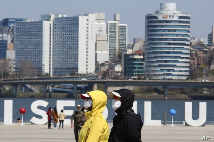 People wearing face masks to help protect against the spread of the new coronavirus walk at a park in Seoul, South Korea,…