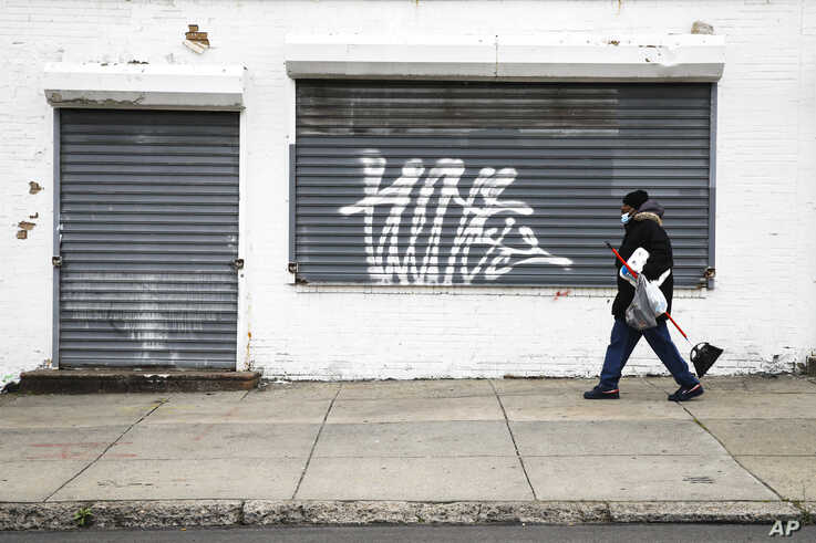 A person wearing a protective face mask as a precaution against the coronavirus walks past a shuttered business in Philadelphia…