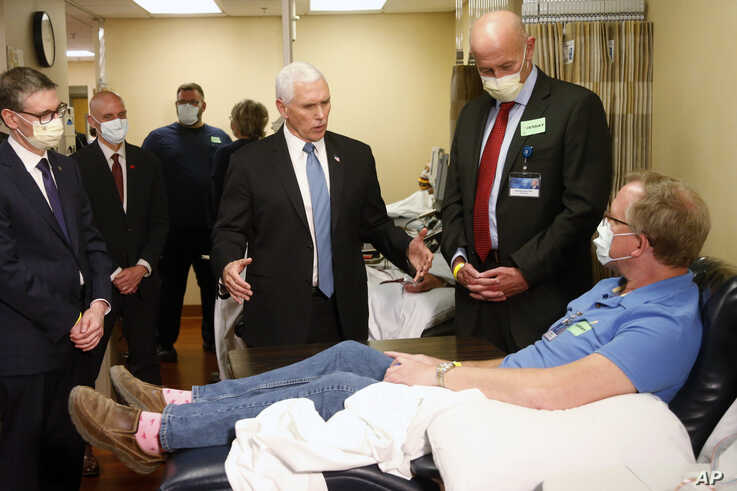 Vice President Mike Pence, center, visits Dennis Nelson, a patient who survived the coronavirus and was going to give blood,…