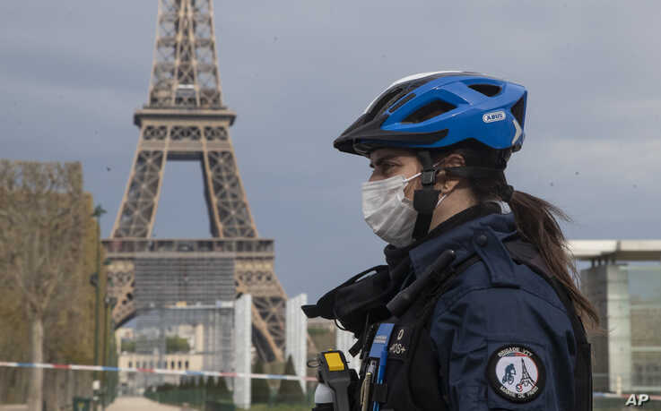 A policewoman wears a mask to protect herself against the spread of the new coronavirus, left, patrols at the garden of the…