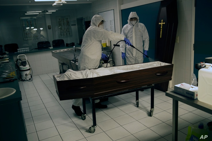 Workers, wearing a full protective equipment, disinfect the casket of someone  who has died of coronavirus at the Fontaine…