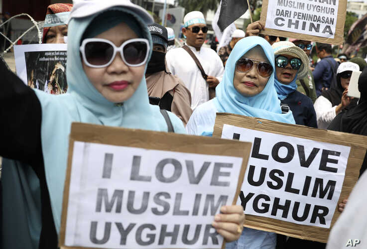 Muslim women hold posters during a rally outside the Chinese Embassy in Jakarta, Indonesia, Friday, Dec. 27, 2019. Over a…