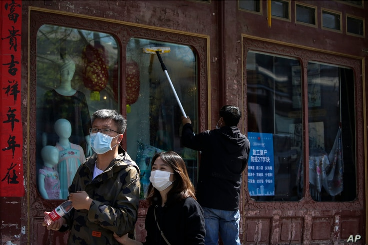 In this April 12, 2020, photo, a Chinese couple walks past a worker wiping window panels at a clothing shop displaying a…