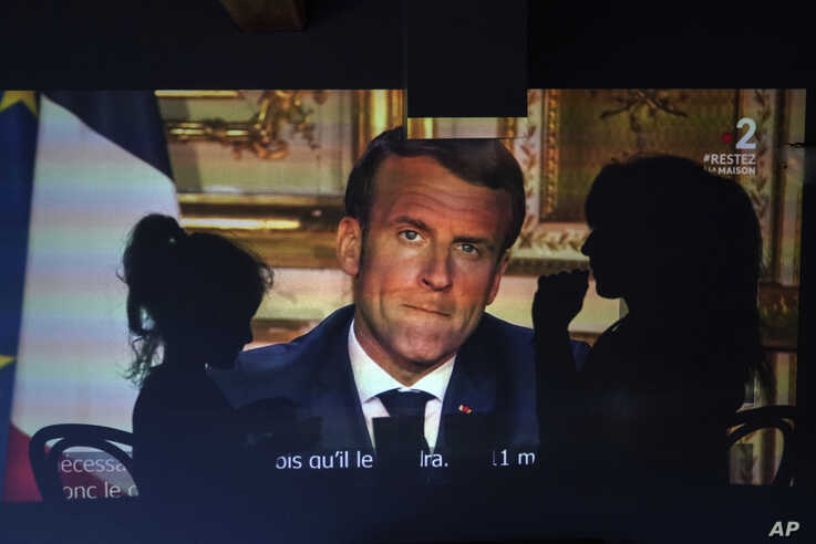 A family watches French President Emmanuel Macron's televised speech, Monday April 13, 2020, in Lyon, central France. French…