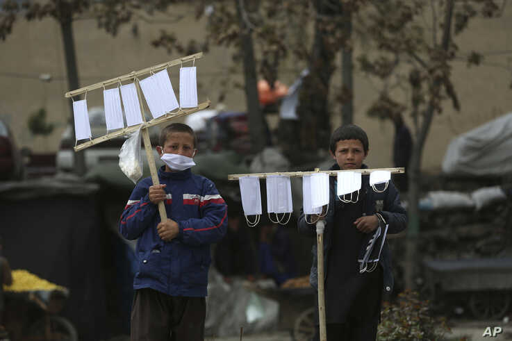 Street vendors selling protective masks to help curb the spread of the new coronavirus wait for customers in Kabul, Afghanistan…