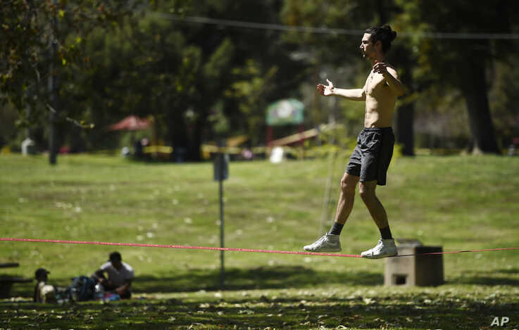 Liam Watkins balances on a slack line at Griffith Park, Thursday, April 16, 2020, in Los Angeles. Watkins said he's been coming…