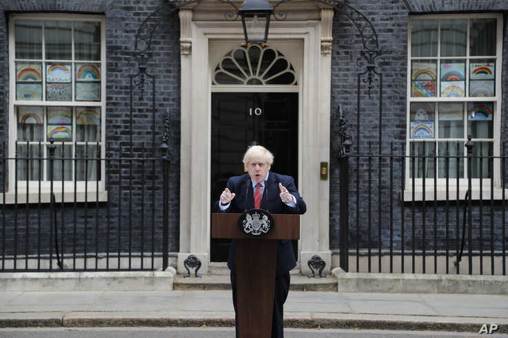 British Prime Minister Boris Johnson makes a statement flanked by children's drawings of rainbows supporting the National…
