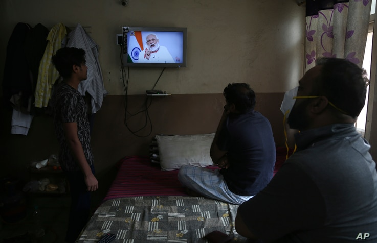 People in Hyderabad, India watch Prime Minister Narendra Modi address the nation in a televised speech about COVID-19 situation…