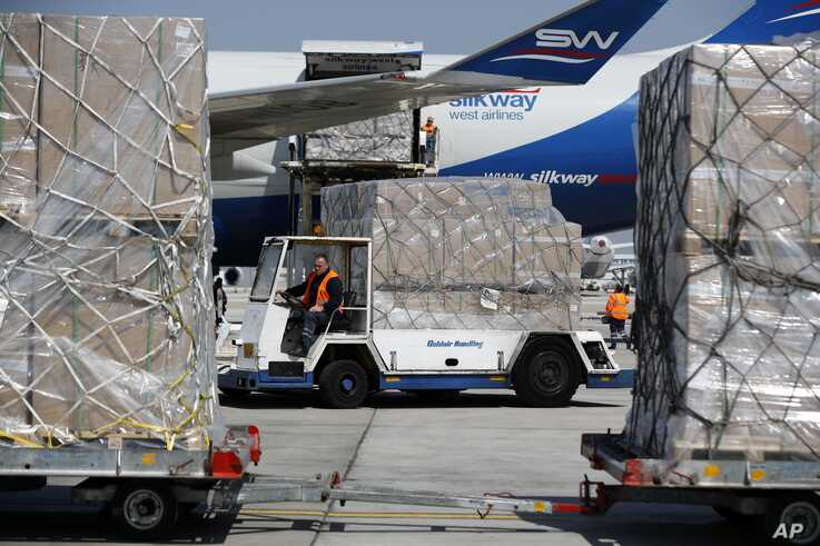Workers unload a cargo plane at Eleftherios Venizelos International Airport in Athens, Tuesday, March 31, 2020. The cargo plane…